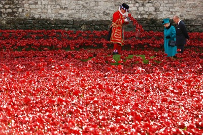 "Britain's Queen Elizabeth and Prince Philip watch a yeoman warder place a wreath in a field of ceramic poppies that form part of the art installation ""Blood Swept Lands and Seas of Red"", at the Tower of London"
